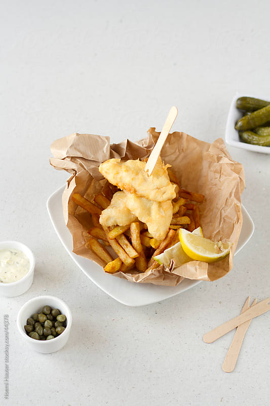 Fish and chips on brown paper with lemon wedges by Noemi Hauser for Stocksy United