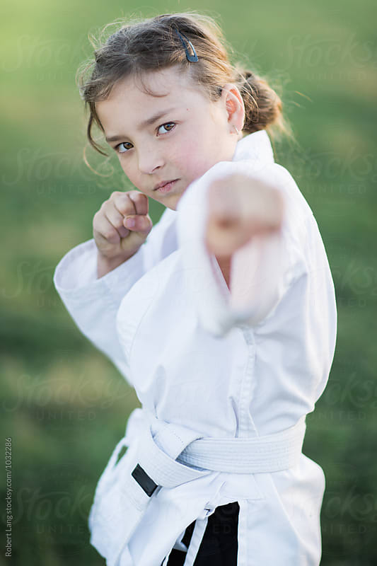 Girl doing martial arts outside on grass by Robert Lang for Stocksy United
