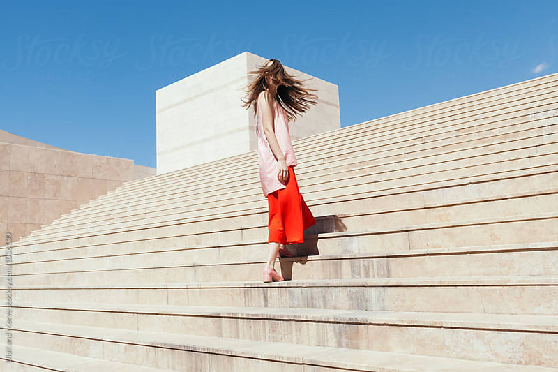 woman with red and pink clothes on the stairs by Ulaş and Merve for Stocksy United