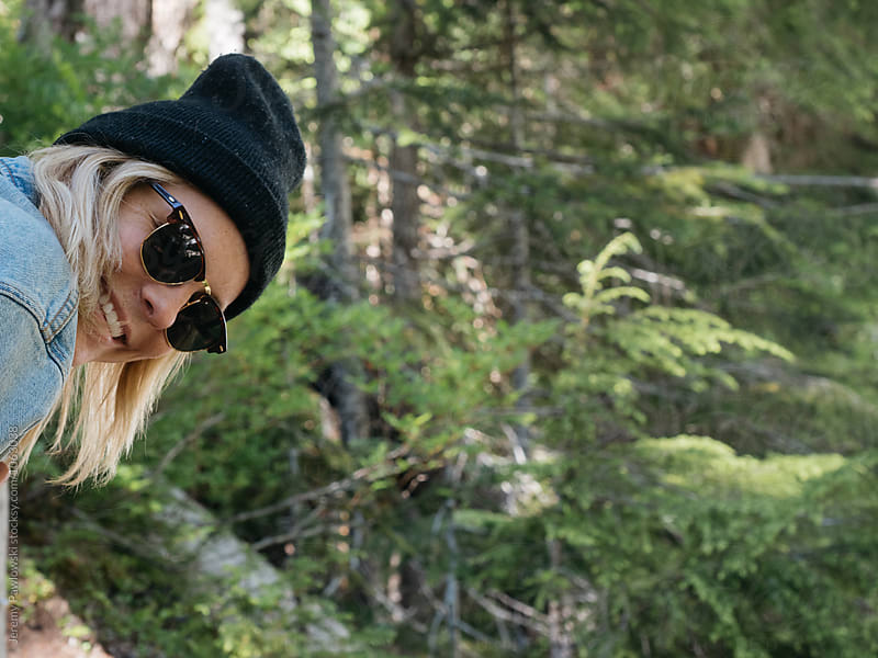 Young woman in beanie and sunglasses smiling while in nature by Jeremy Pawlowski for Stocksy United