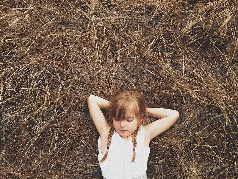 Young girl laying in field with arms crossed  by Kristin Rogers Photography for Stocksy United