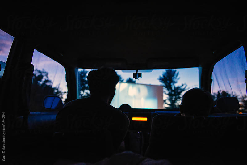 Boy and his dad watch a drive-in movie together in the car on a summer night by Cara Dolan for Stocksy United