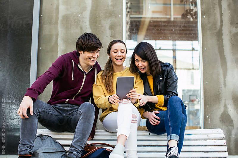 Friends watching a funny video on their digital tablet. by BONNINSTUDIO for Stocksy United