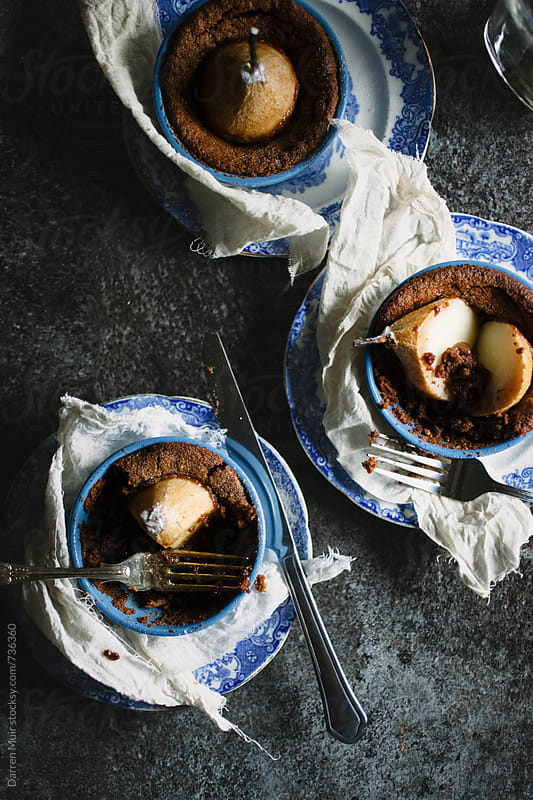 Chocolate and pear puddings on a table: seen from above. by Darren Muir for Stocksy United