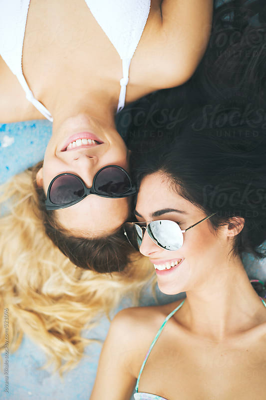 Two female friends enjoying the day on the swimming pool by Jovana Rikalo for Stocksy United