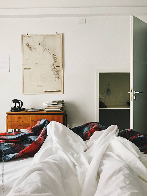 Lazy Day - Legs of Person Lying in Bed Under White Bedsheet by Julien L. Balmer for Stocksy United