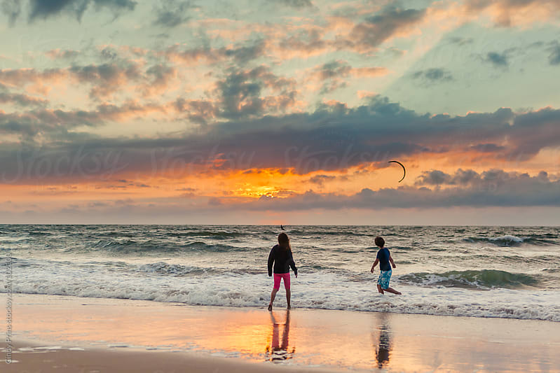 Boy and girl playing on the beach during sunset watching a kite surfer by Cindy Prins for Stocksy United
