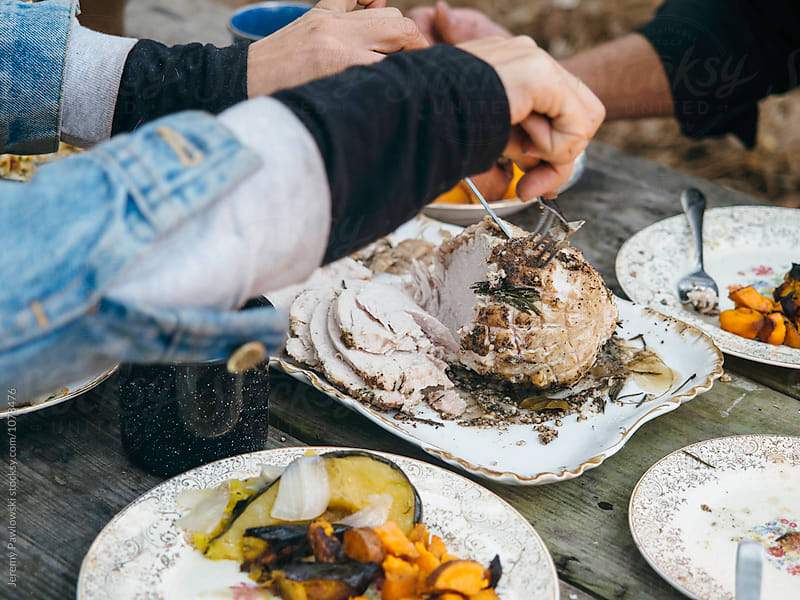Carving a turkey for rustic outdoor Thanksgiving dinner by Jeremy Pawlowski for Stocksy United