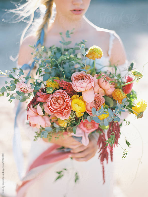 spring time floral design in wedding gown with bride in gown on beach by wendy laurel for Stocksy United
