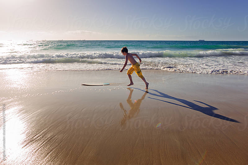 Boy catching a ride on a skim board at the beach by Angela Lumsden for Stocksy United