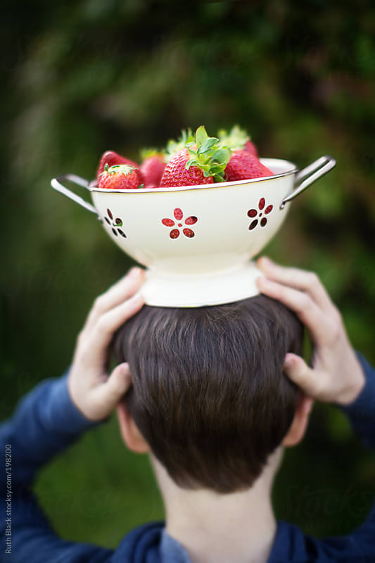 Boy holding colander filled with strawberries on his head by Ruth Black for Stocksy United