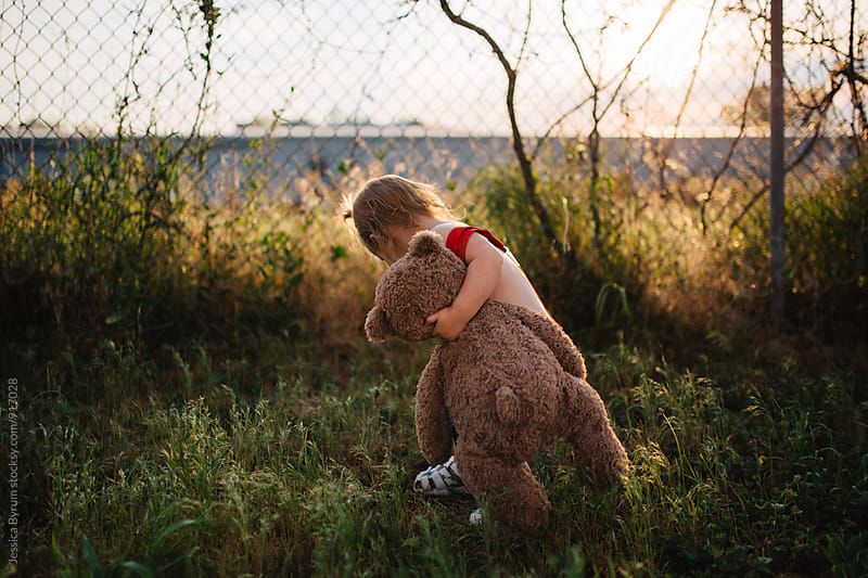 Cute toddler girl in red suspenders exploring while holding a teddy bear. by Jessica Byrum for Stocksy United