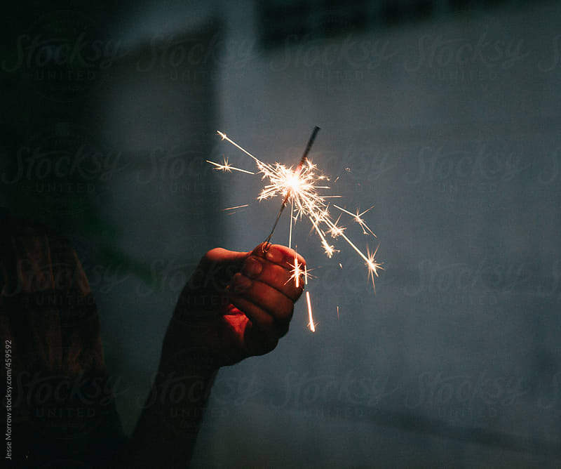 Young man holding sparkler by Jesse Morrow for Stocksy United