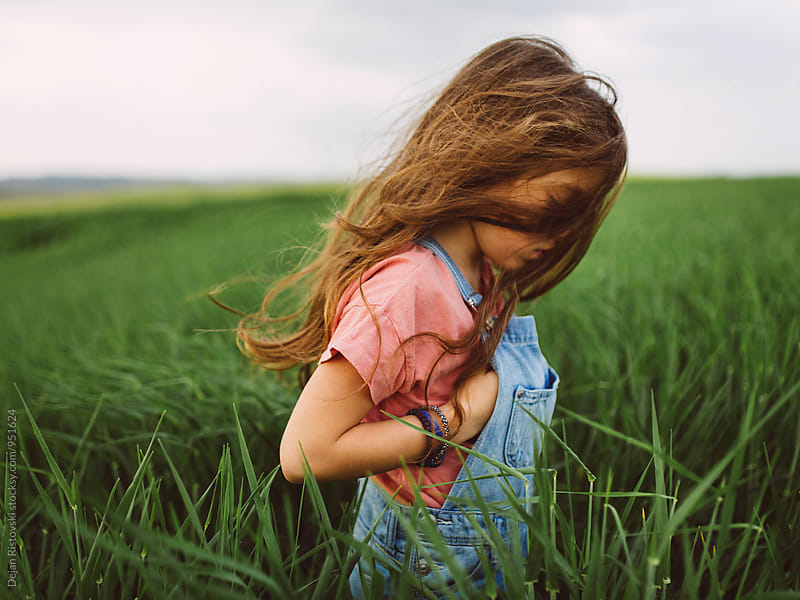 Child in wheat field. by Dejan Ristovski for Stocksy United