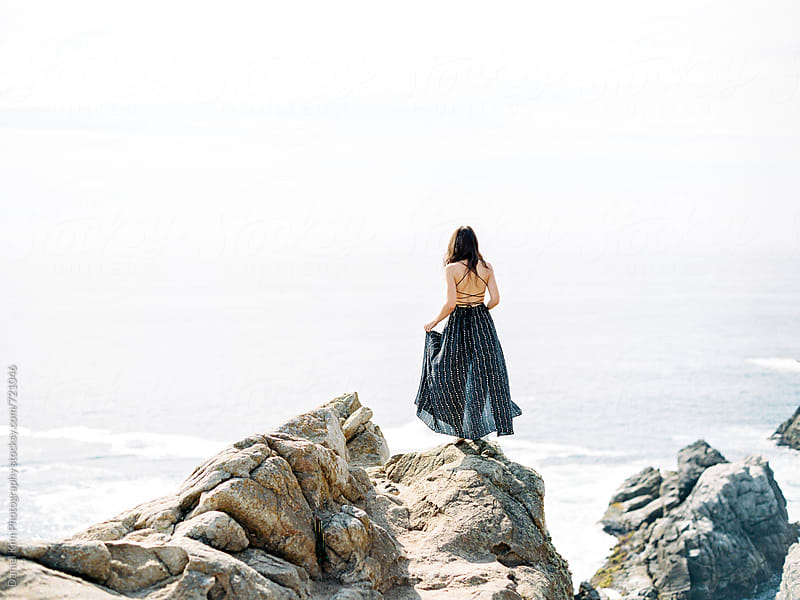 Woman standing on ocean cliff by Daniel Kim Photography for Stocksy United