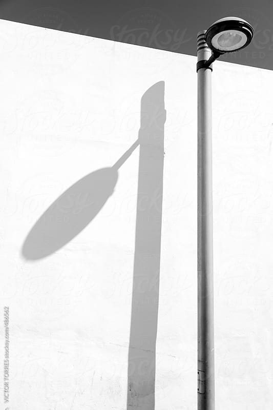Street Lamp Shadow over a White Wall by VICTOR TORRES for Stocksy United