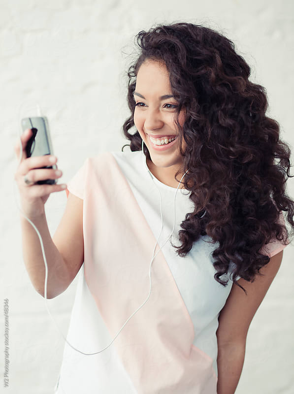 Young woman videochatting with friends on smartphone. by W2 Photography for Stocksy United