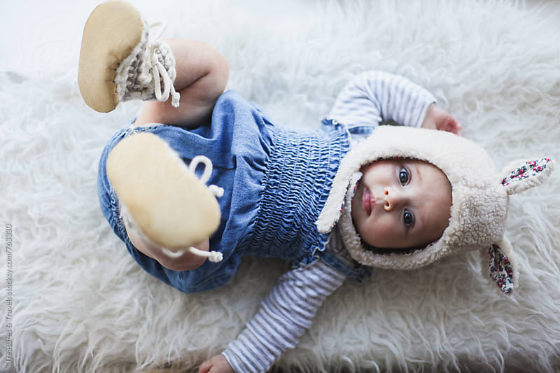 Cute baby girl laying on sheepskin by Treasures & Travels for Stocksy United