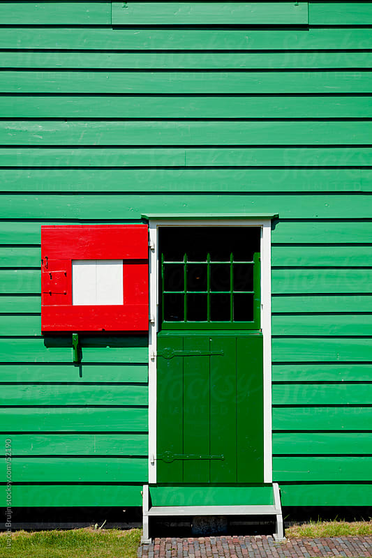 A green wooden house with a green door and a red shutter or hatch by Ivo de Bruijn for Stocksy United