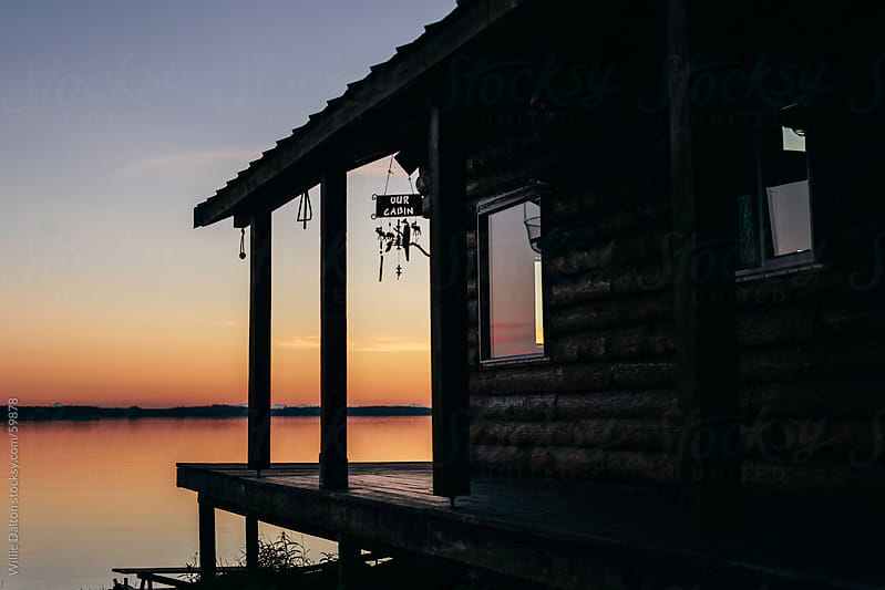 Log Cabin Silhouetted by Sky at Twilight by Willie Dalton for Stocksy United