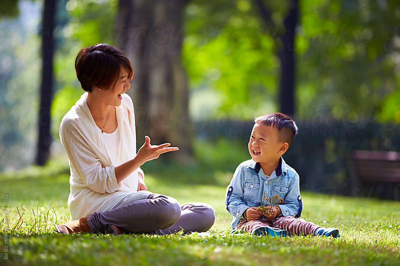 happy asian mother with her boy in the sunny park by Bo Bo for Stocksy United