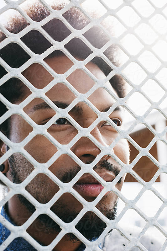 Closeup portrait of an african american man through a fence. by BONNINSTUDIO for Stocksy United
