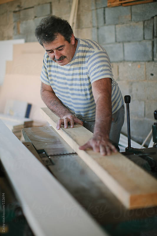 Carpenter Sawing a Board by Zocky for Stocksy United