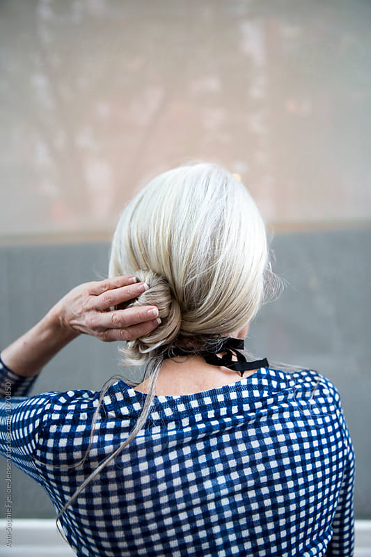 Woman fixing her hair by Ann-Sophie Fjelloe-Jensen for Stocksy United