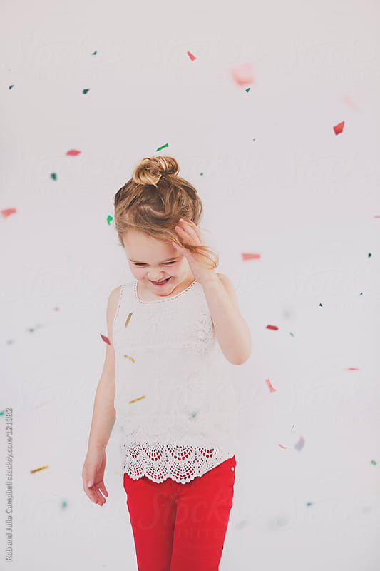 Candid moment as holiday confetti falls down by Rob and Julia Campbell for Stocksy United