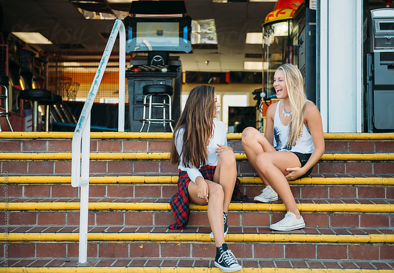 Two teenagers chatting and sitting on steps outside of an arcade by Emmanuel Hidalgo for Stocksy United