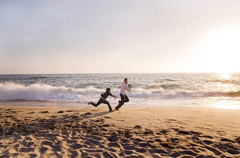 Father and Son Playing Football On Beach by Dina Giangregorio for Stocksy United