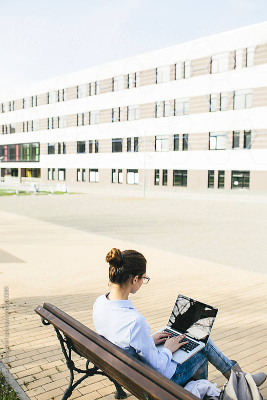 Young businesswoman wworking on laptop, outdoors by Aleksandar Novoselski for Stocksy United