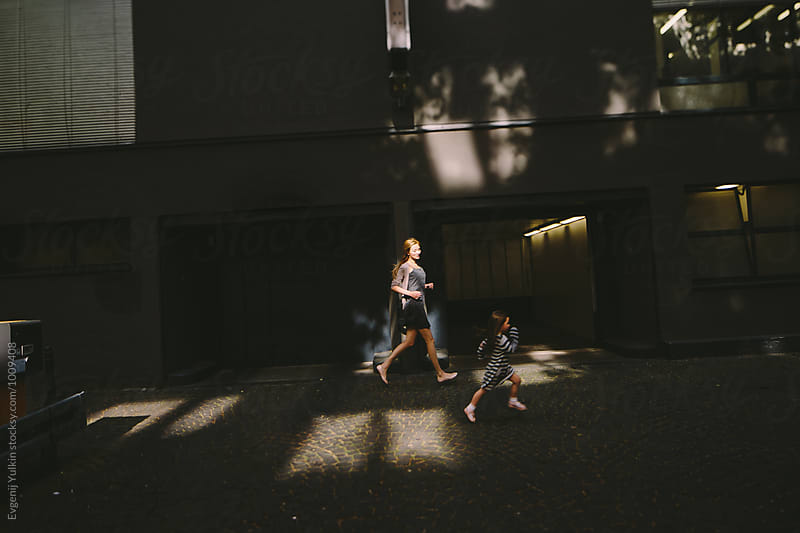 Mother and daughter running through the sunbeam along the street by Evgenij Yulkin for Stocksy United