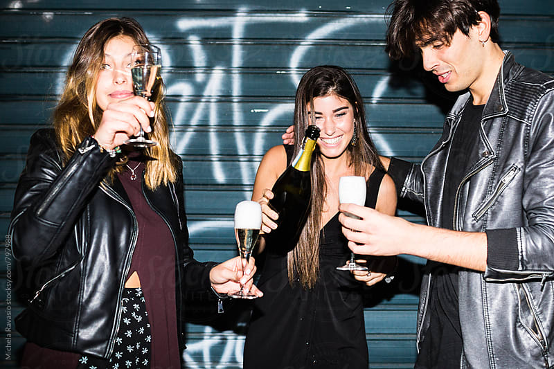 Group of friends celebrating with champagne at a party by michela ravasio for Stocksy United