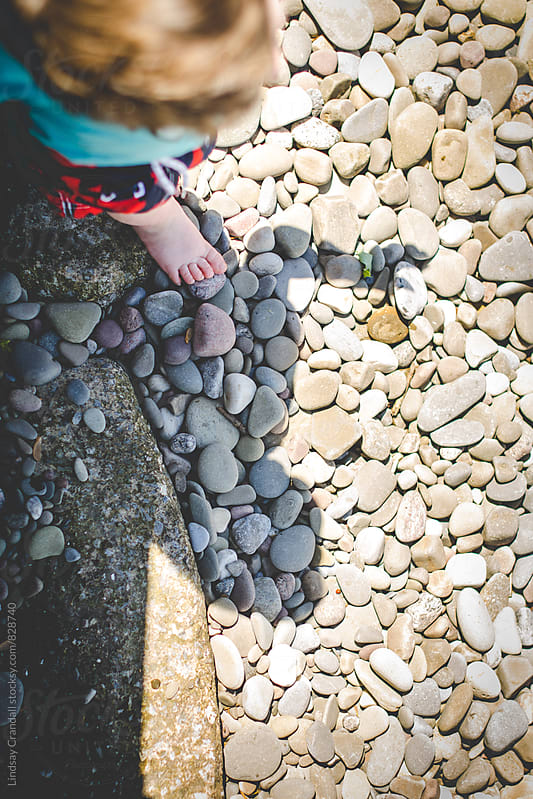 Looking down on boy standing on stone beach in summer by Lindsay Crandall for Stocksy United