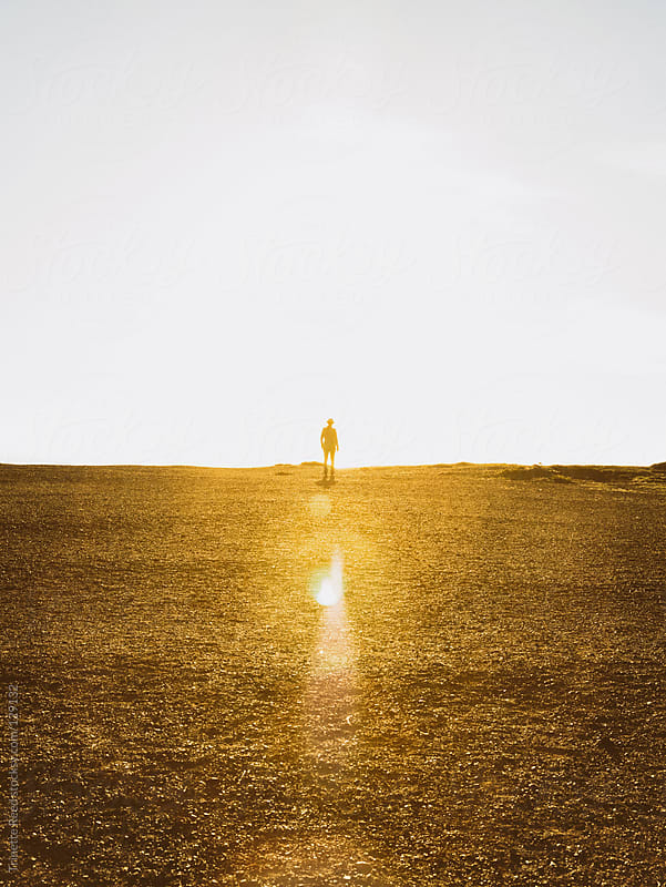 Person walking into light by Trinette Reed for Stocksy United