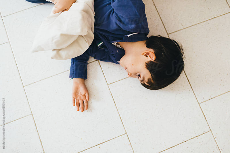 Child playing lying on the floor by michela ravasio for Stocksy United