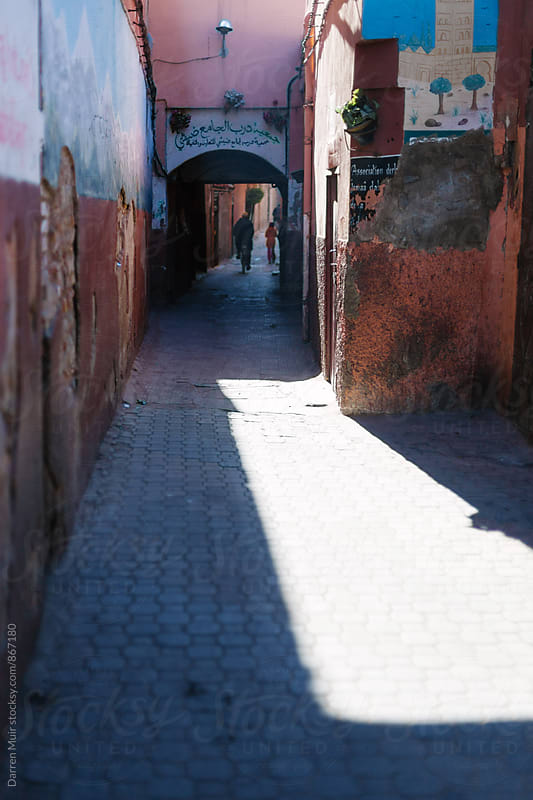 Side street in Marrakesh with graffiti and unrecognizable people in the distance. by Darren Muir for Stocksy United