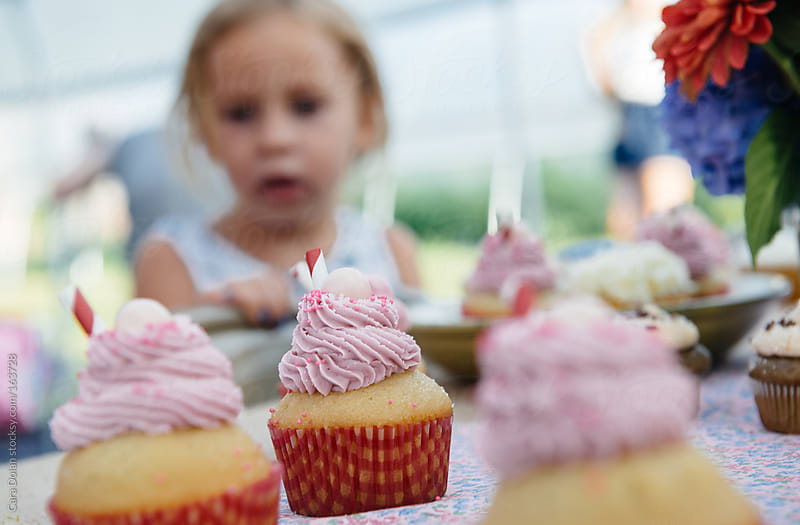 Little girl at a party looks at a table filled with cupcakes by Cara Dolan for Stocksy United