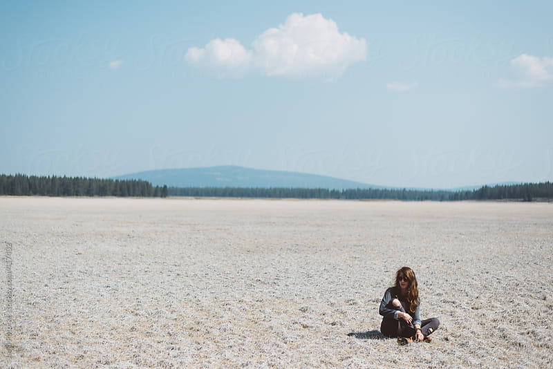 Young woman sitting in open field by Jacki Potorke for Stocksy United