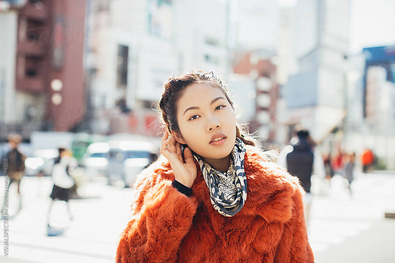 Outdoor Portrait of Young Pretty Asian Woman in Red Fur Coat Touching Her Head by Julien L. Balmer for Stocksy United