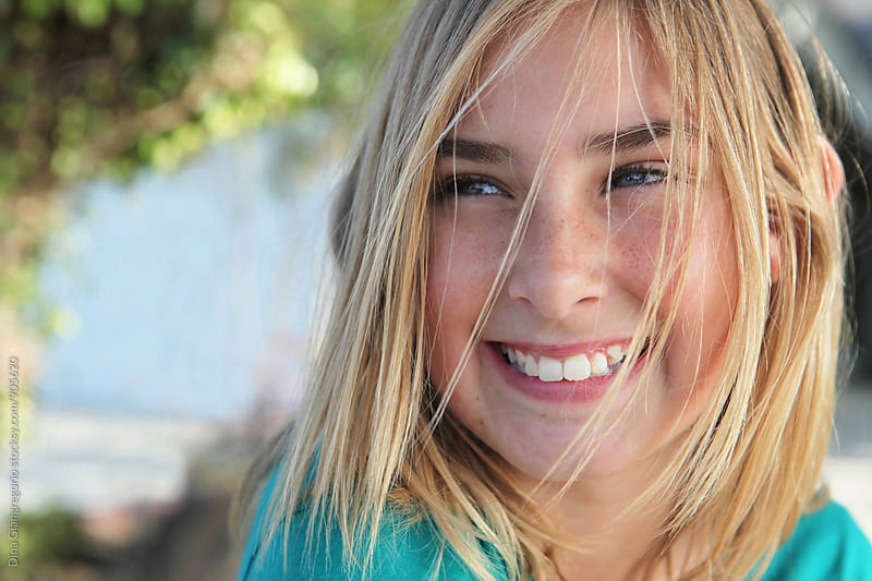 Young Blonde Girl Laughing With Hair In Face by Dina Giangregorio for Stocksy United