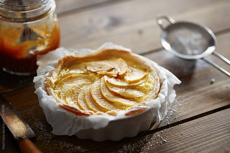 Apple tart on paper in its mold by Martí Sans for Stocksy United