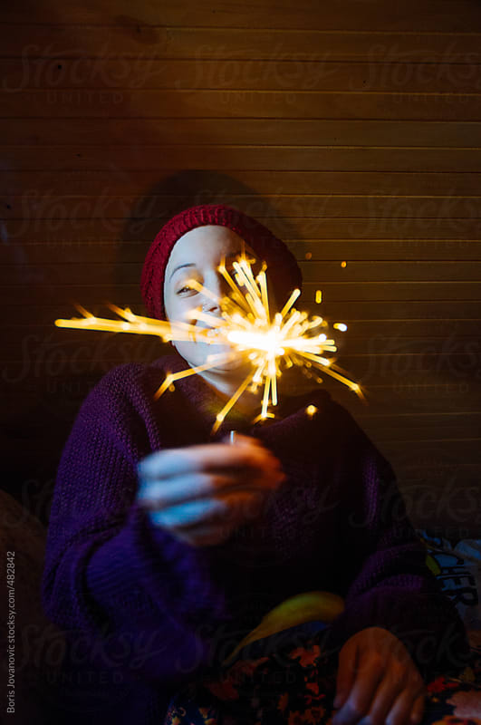 Young female holding sparkles and smiling by Boris Jovanovic for Stocksy United