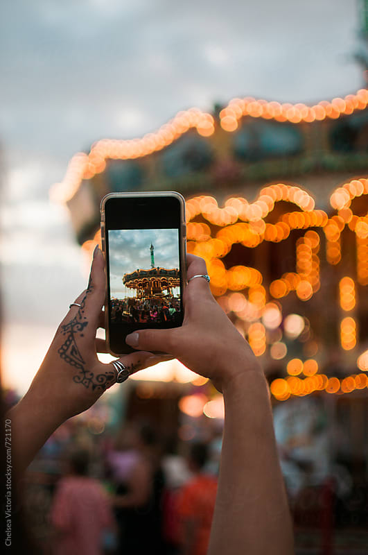 A young woman taking pictures on her phone of a carousel by Chelsea Victoria for Stocksy United