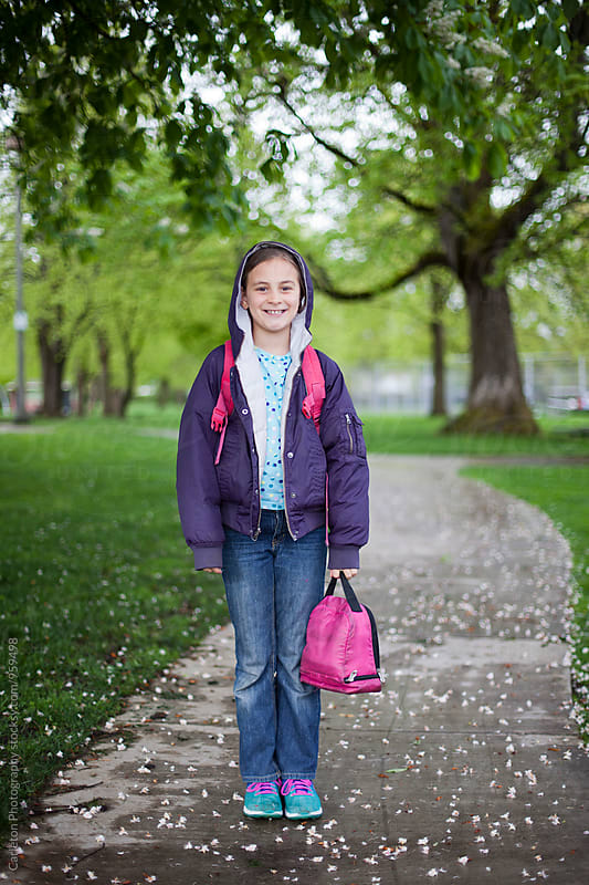Schoolgirl with purple jacket and pink lunch bag by Carleton Photography for Stocksy United