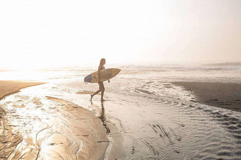 young woman walking on beach with surfboard by Felix Hug for Stocksy United