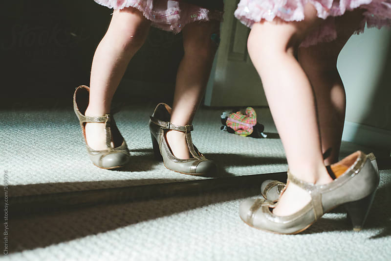 A little girl is wearing women's high heels as looks in the mirror. by Cherish Bryck for Stocksy United