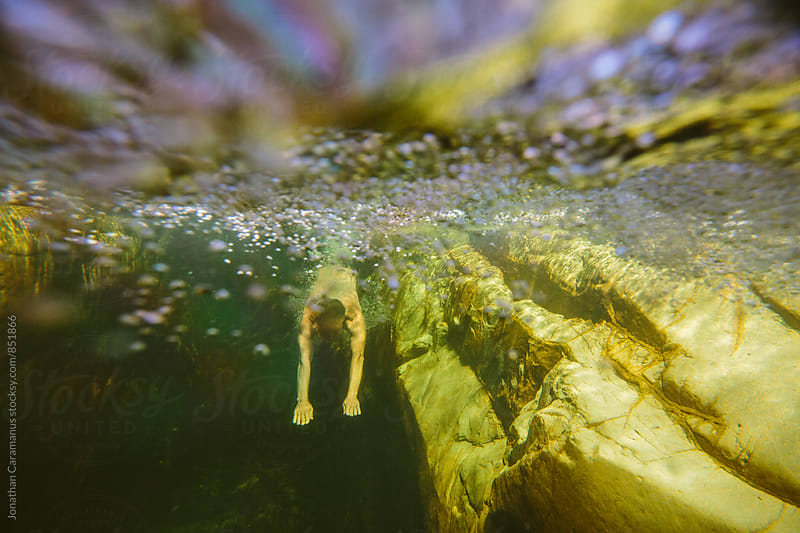 Man dives into rockpool water leaving a trail of bubbles  by Jonathan Caramanus for Stocksy United