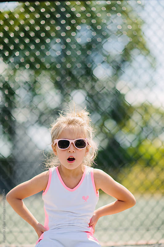 girl with sunglasses looks surprised sitting next to tennis court by Rebecca Zeller for Stocksy United